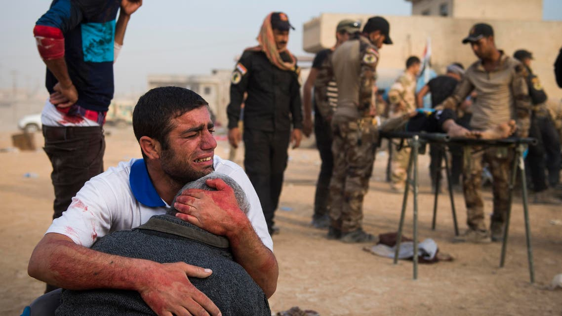Father and grandfather of 15-year-old Shafiq mourn as Iraqi forces surround his body at an outdoor field clinic in the Samah neighbourhood in Mosul on November 13, 2016. A double barreled mortar attack killed Shafiq and seriously injured his 12-year-old neighbour Mohammed as Iraqi Special Forces 2nd division continued to battle IS forces as they pushed through the Arbagiah area and into the neigbourhood of Karkukli.  Odd ANDERSEN / AFP