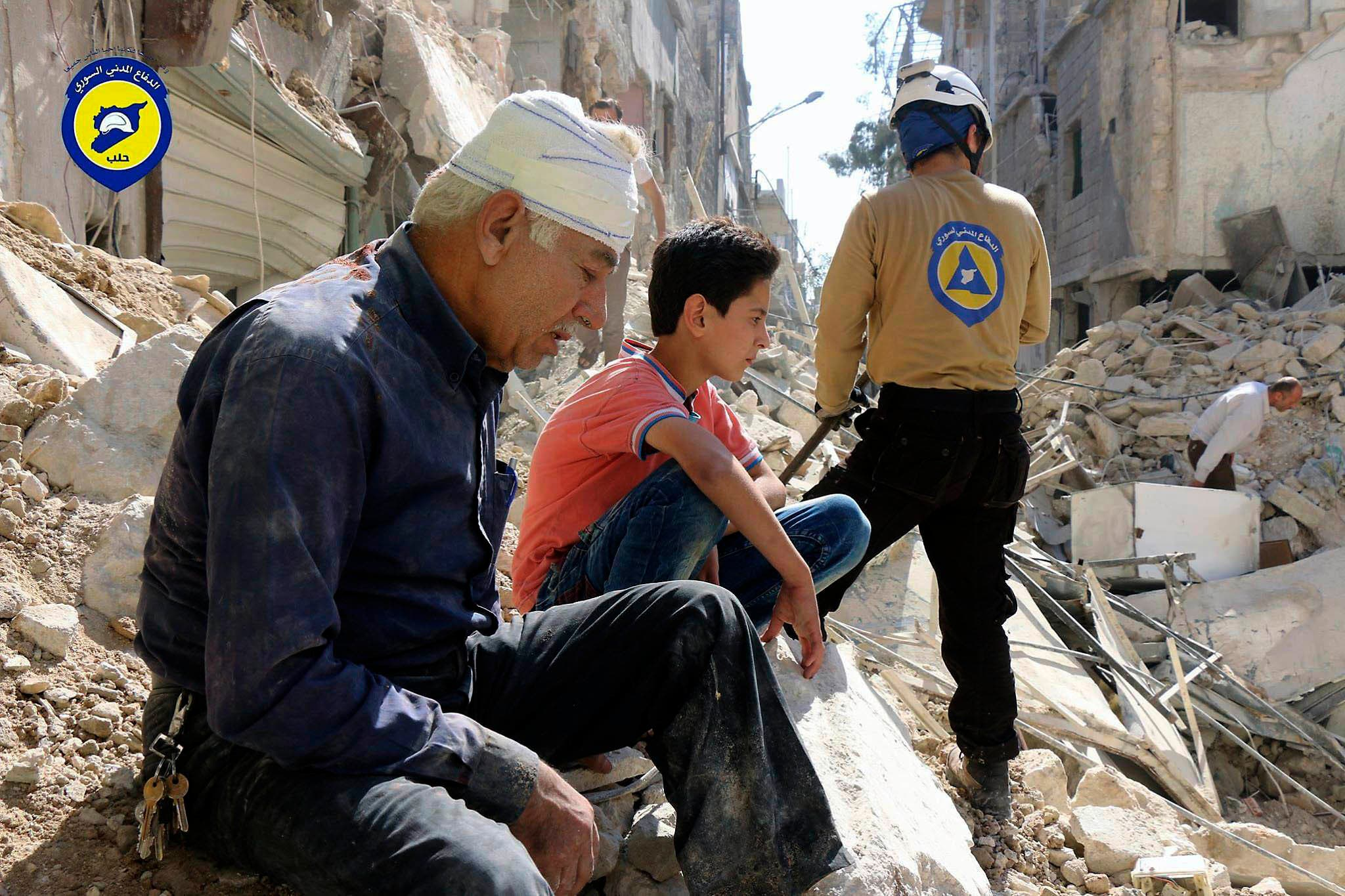 In this Oct. 11, 2016 file photo, provided by the Syrian Civil Defense group known as the White Helmets, residents sit amongst rubble in rebel-held eastern Aleppo, Syria.  AP
