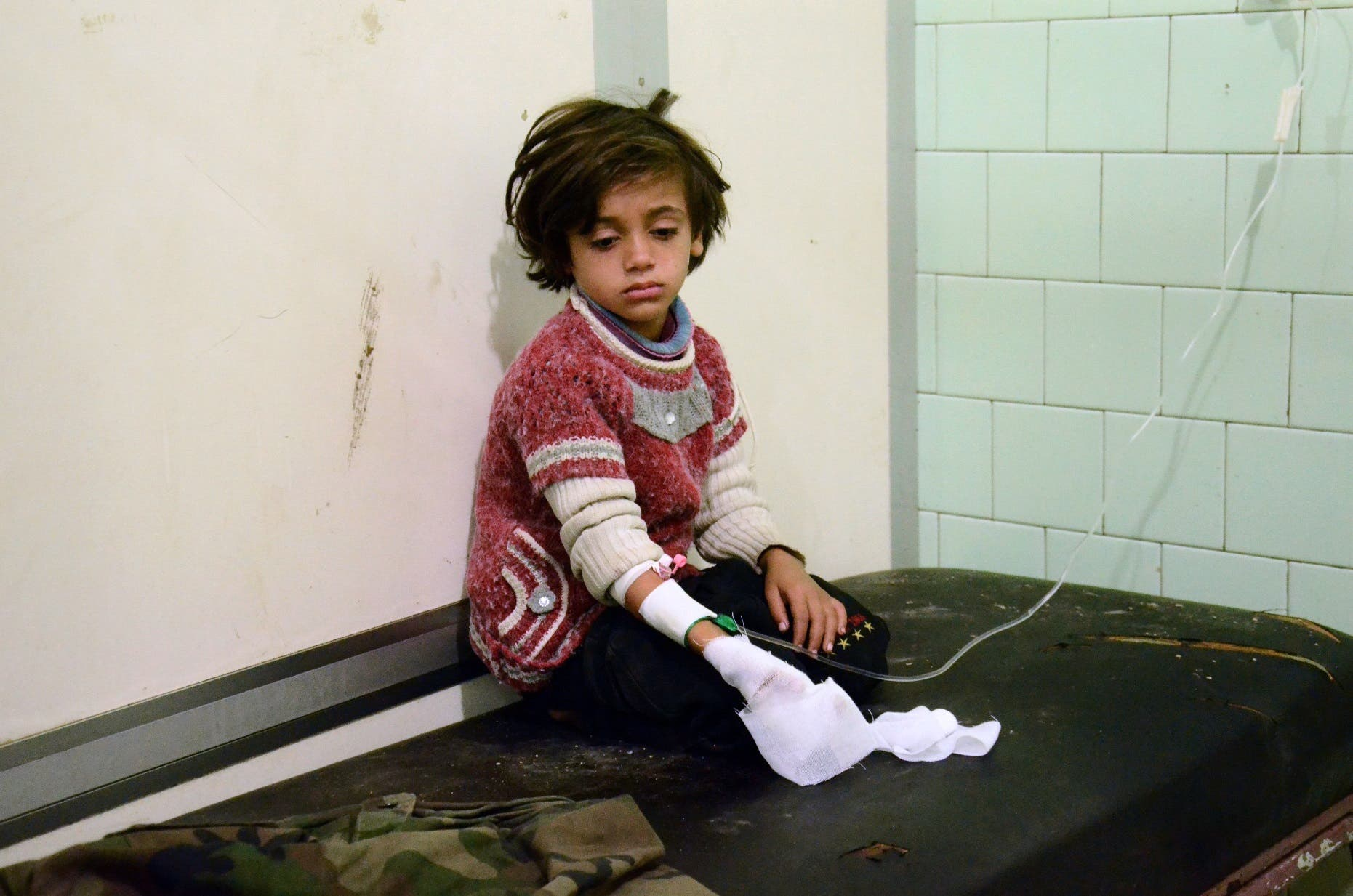 An injured child waits after receiving treatment at the University hospital in a government-held neighbourhood on November 3, 2016 following reported rebel fire on government-held parts of the northern city of Aleppo. Rebel fire on government-held parts of Syria's Aleppo killed 12 civilians and wounded 200, state news agency SANA reported. The Syrian Observatory for Human Rights gave a toll of 11 civilians killed, including four children, and at least 100 people wounded.  GEORGE OURFALIAN / AFP