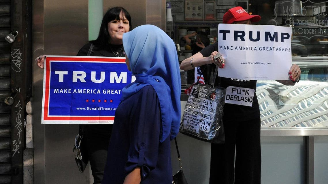 A woman wearing a Muslim headscarf walks past people holding Donald Trump signs before the annual Muslim Day Parade in the Manhattan. (Reuters)