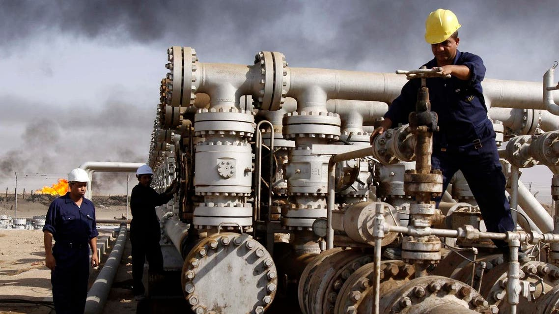 In this Dec. 13, 2009 file photo, Iraqi workers are seen at the Rumaila oil refinery, near the city of Basra, 340 miles (550 kilometers) southeast of Baghdad, Iraq. Plunging oil prices have pitched Iraq into a severe financial crisis as it struggles to combat the Islamic State group, play host to millions of refugees and rebuild cities and towns ravaged by war. With global prices hovering around $30 a barrel, Iraq has had to draw on foreign exchange reserves to fill a shortfall in the 2016 budget, which anticipated $45 per barrel. (AP