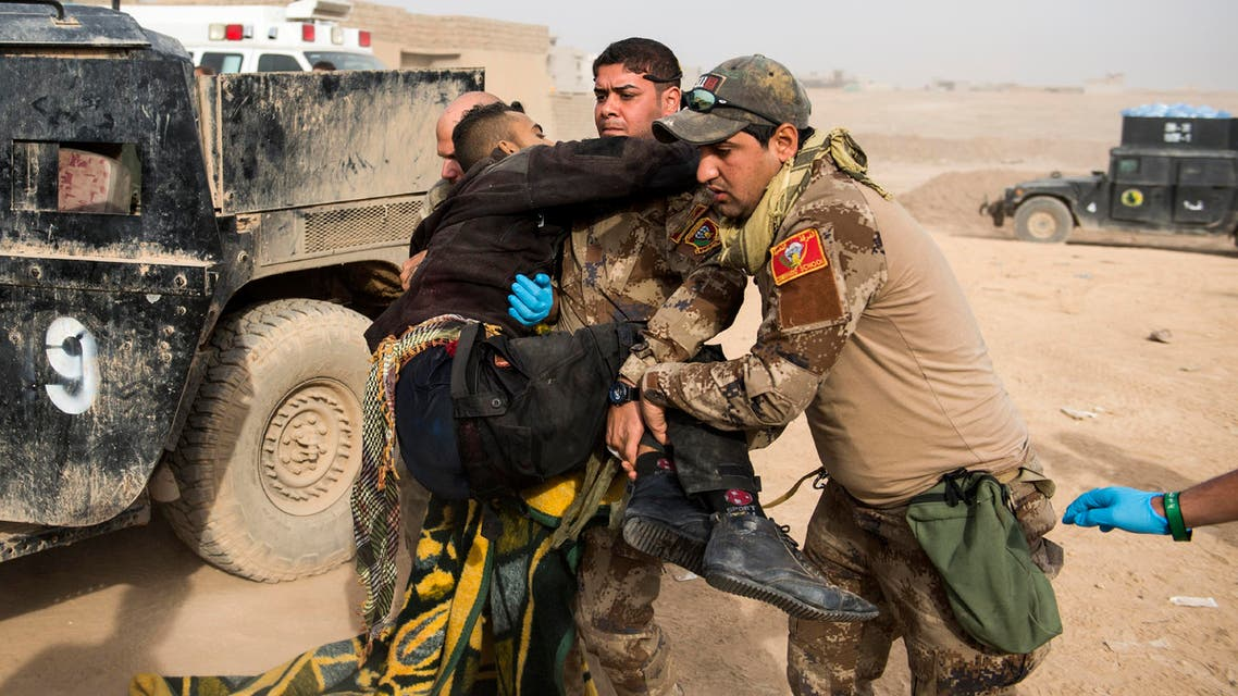 Frontline medics help carry an Iraqi soldier hit by sniper fire in his pelvis area out of their vehicle at an Iraqi Special Forces 2nd division outdoor field clinic in the Samah neighbourhood of Mosul on November 15, 2016.  Odd ANDERSEN / AFP