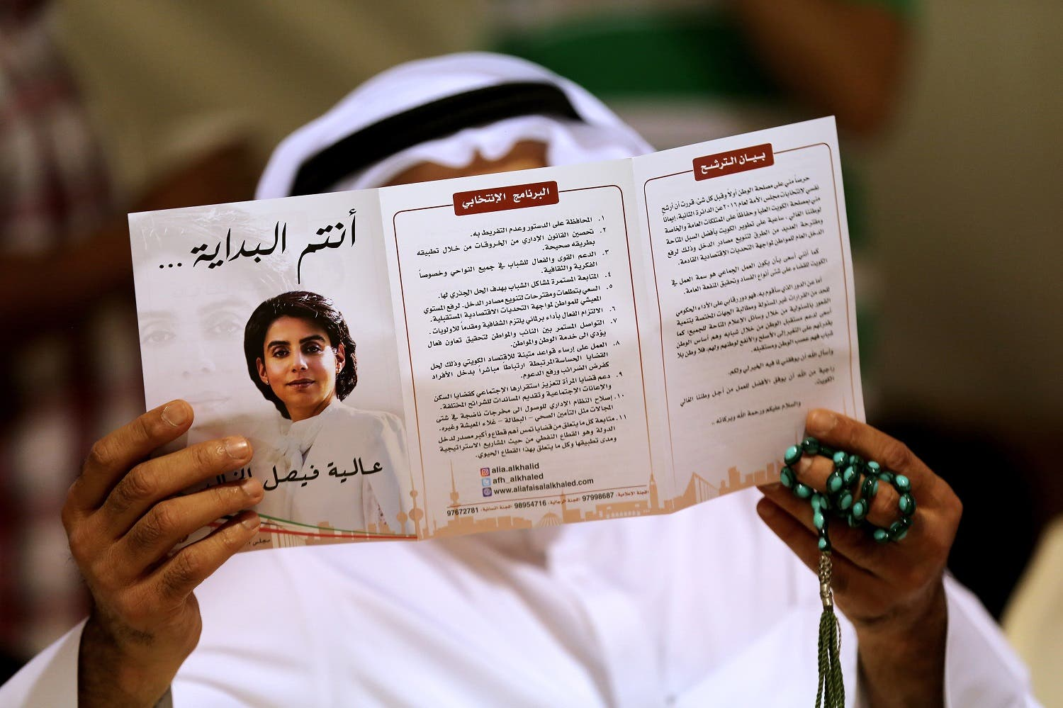 A Kuwaiti man holds a brochure as he attends a campaign meeting for Kuwaiti female candidate Alia al-Khaled. (AFP)