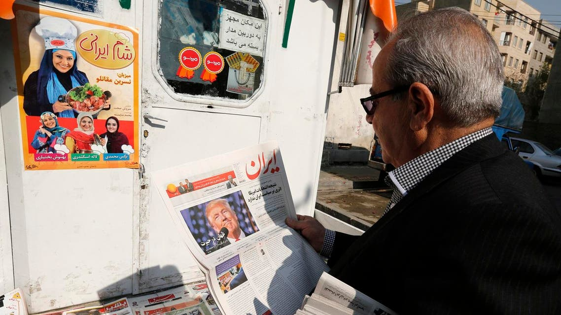 An Iranian man holds a local newspaper displaying a portrait of Donald Trump a day after his election as the new US president, in the capital Tehran, on November 10, 2016 AFP