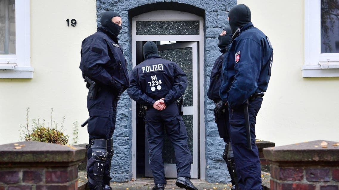 AP Police officers seach a residential building opposite the German-Speaking Islamic Circle Hildesheim mosque in Hildesheim, Germany, Tuesday, Nov. 8, 2016.