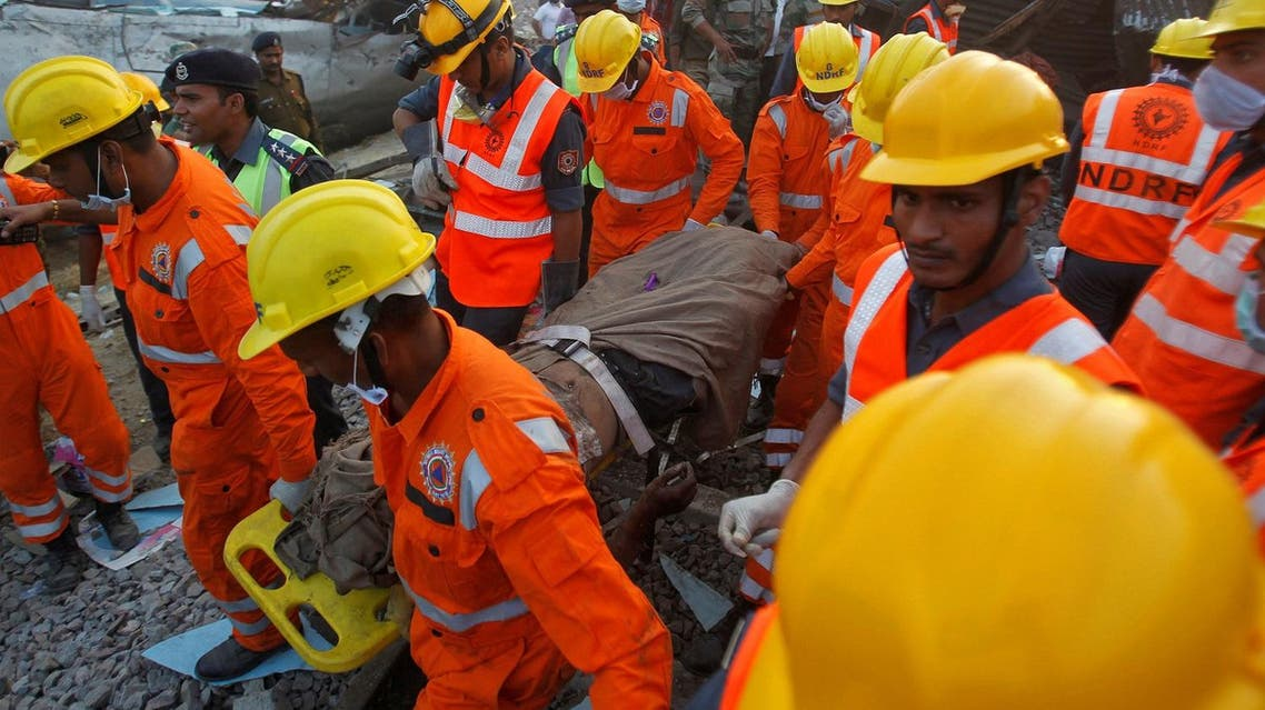 Rescue workers remove the remains of a passenger from the site of a train derailment in Pukhrayan, south of Kanpur city, India. (Reuters)