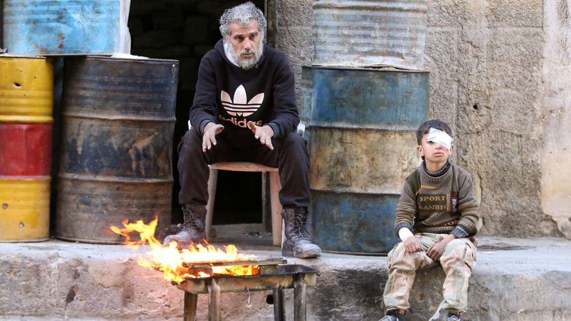 An injured boy sits near a man as they warm themselves by a fire in a rebel held area of Aleppo, Syria November 18, 2016. REUTERS/Abdalrhman Ismail