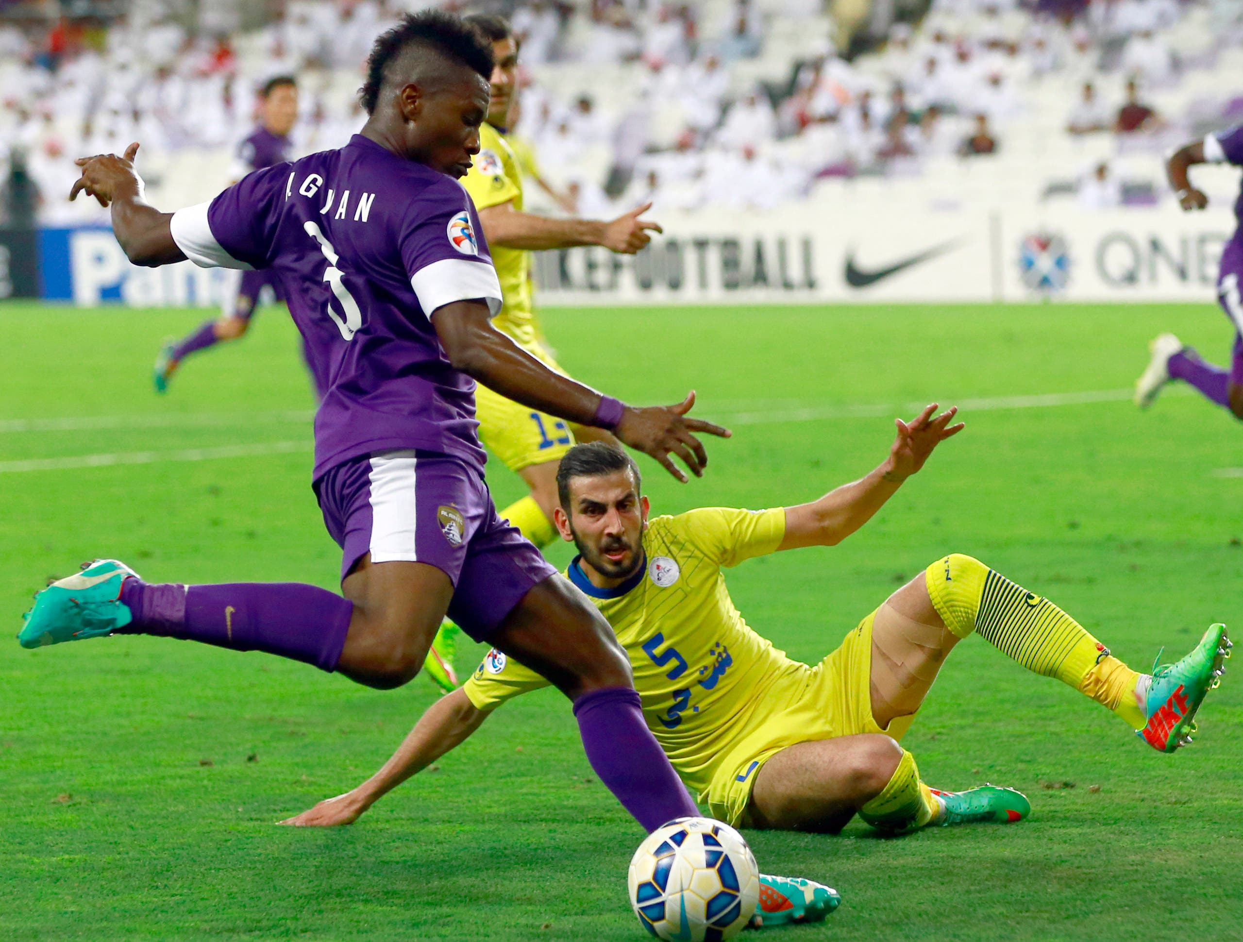 Al-Ain's Asamoah Gyan (L) fights for the ball with Naft's Amin Hajmohammadi (R) during their AFC Champions League Group B football match Iran's Naft Tehran against UAE's Al-Ain at Sheik Hazza Bin Zayed stadium on May 6, 2015 in Al-Ain. AFP