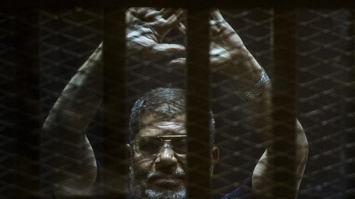 A file picture taken on June 2, 2015 shows ousted Egyptian president Mohamed Morsi gesturing from the defendants' cage as he attends his trial at the police academy on the outskirts of the capital Cairo. (AFP)