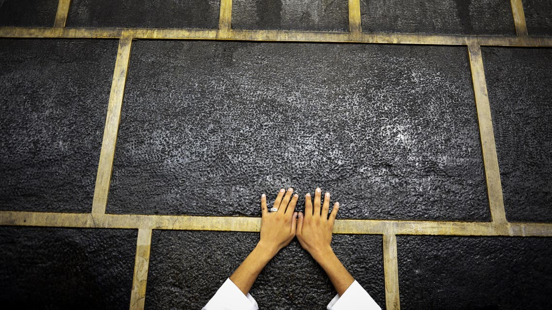 A muslim pilgrim touches Islam's holiest shrine, the Kaaba, at the Grand Mosque in the Saudi holy city of Mecca, late on September 21, 2015. The annual hajj pilgrimage begins on September 22, and more than a million faithful have already flocked to Saudi Arabia in preparation for what will for many be the highlight of their spiritual lives. AFP PHOTO / MOHAMMED AL-SHAIKH  MOHAMMED AL-SHAIKH / AFP