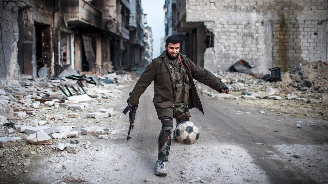 A Syrian rebel plays football in the Saif al-Dawlah neighborhood of Aleppo, Syria, Wednesday, Jan. 2, 2013. AP