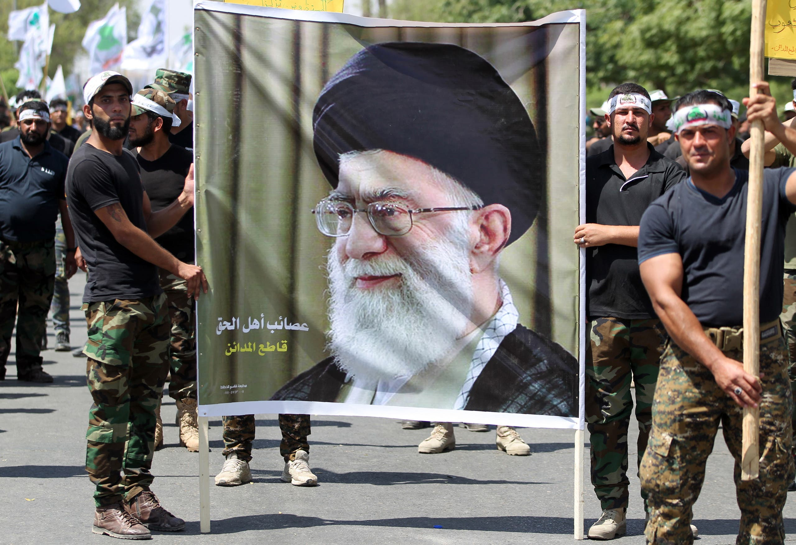 Iraqi pro-government forces hold a poster bearing a portrait of Iran's supreme leader Ayatollah Ali Khamenei as they take part in a parade marking al-Quds Day in Baghdad, on July 1, 2016. (AFP)