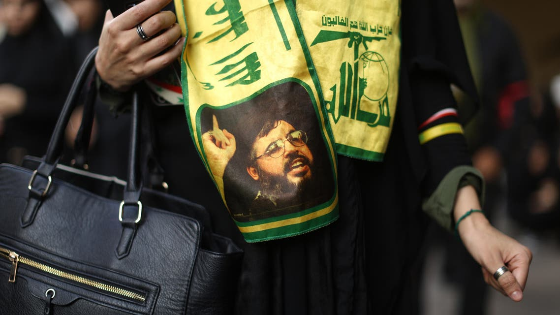 A woman wears a scarf decorated in the colours of Lebanon's Shiite Hezbollah movement and bearing a picture of the movement's leader Hassan Nasrallah as she takes part in commemorations marking Ashura in a Beirut southern suburb on October 12, 2016. Ashura mourns the death of Imam Hussein, a grandson of the Prophet Mohammed, who was killed by armies of the Yazid near Karbala in 680AD. PATRICK BAZ / AFP