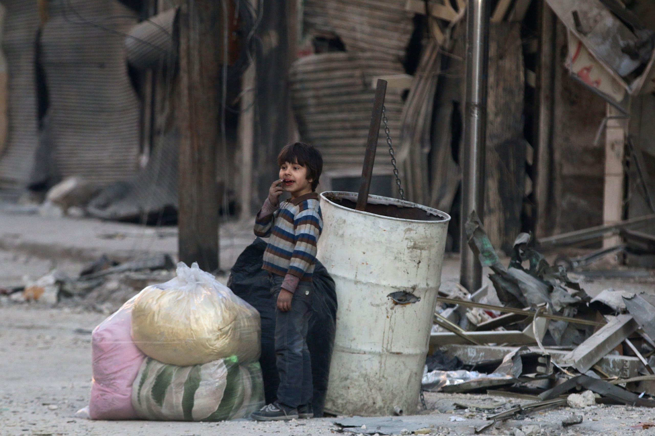 A boy stands amid the damage in the rebel-held besieged al-Shaar neighborhood of Aleppo, Syria November 23, 2016. REUTERS/Abdalrhman Ismail