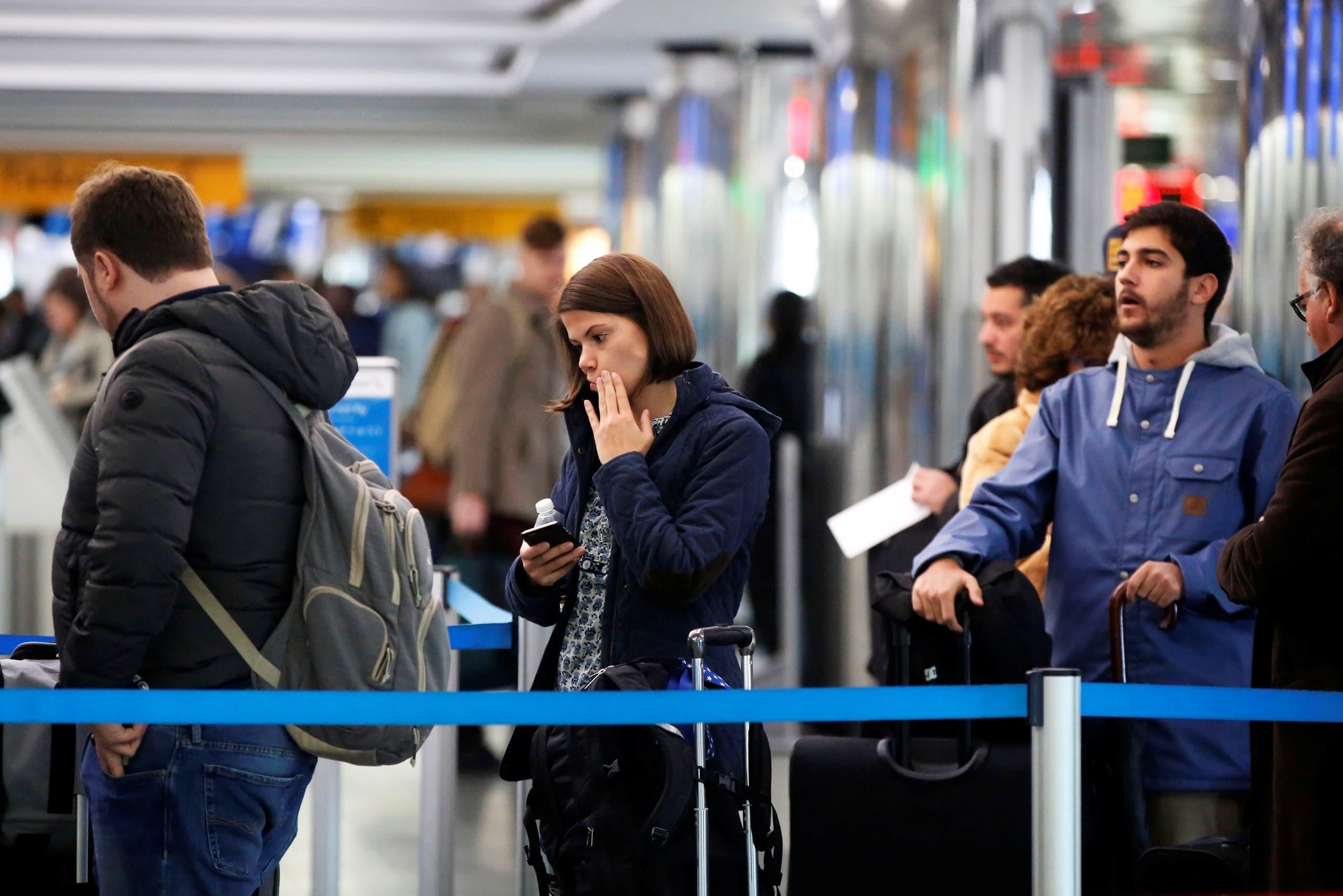 مسافرون ينتظرون في مطار لاغوارديا في نيويورك