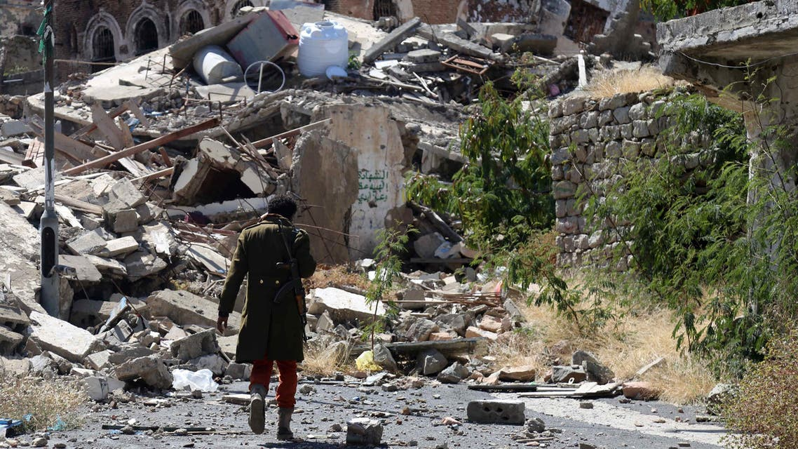 A Yemeni man inspects the damage on a street following clashes between pro-government militants, loyal to President Abedrabbo Mansour Hadi, and Houthi rebels on November 22, 2016 in Taiz. (AFP)