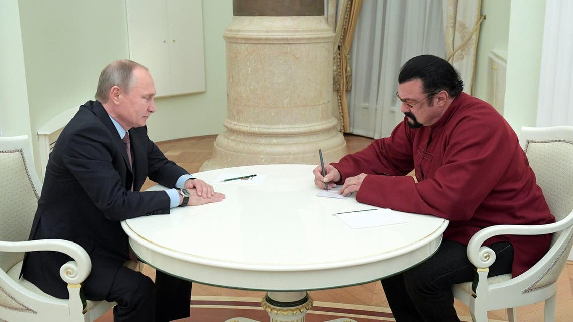Steven Seagal (R) signs a Russian passport received from Russia's President Vladimir Putin during a meeting at the Kremlin in Moscow. (Reuters)