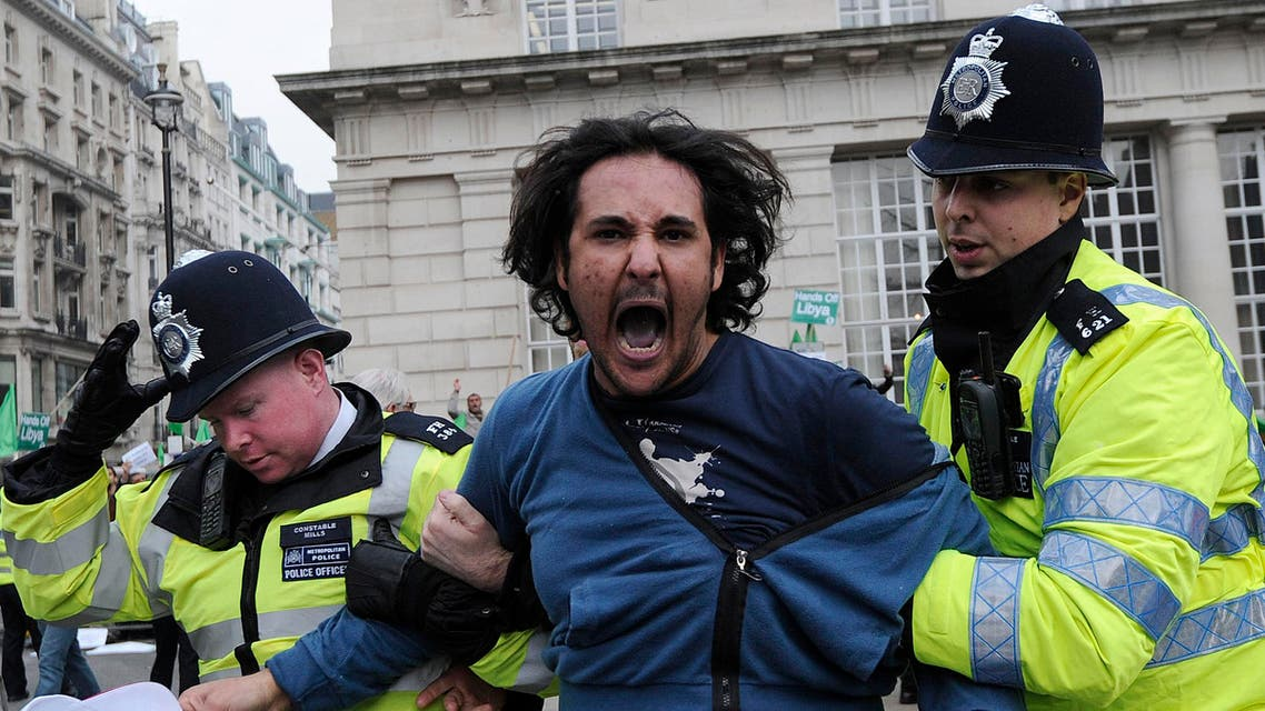 A protestor (C) is led away by police while taking part in a pro-Qaddafi demonstration in London, on March 29, 2011. (AFP)