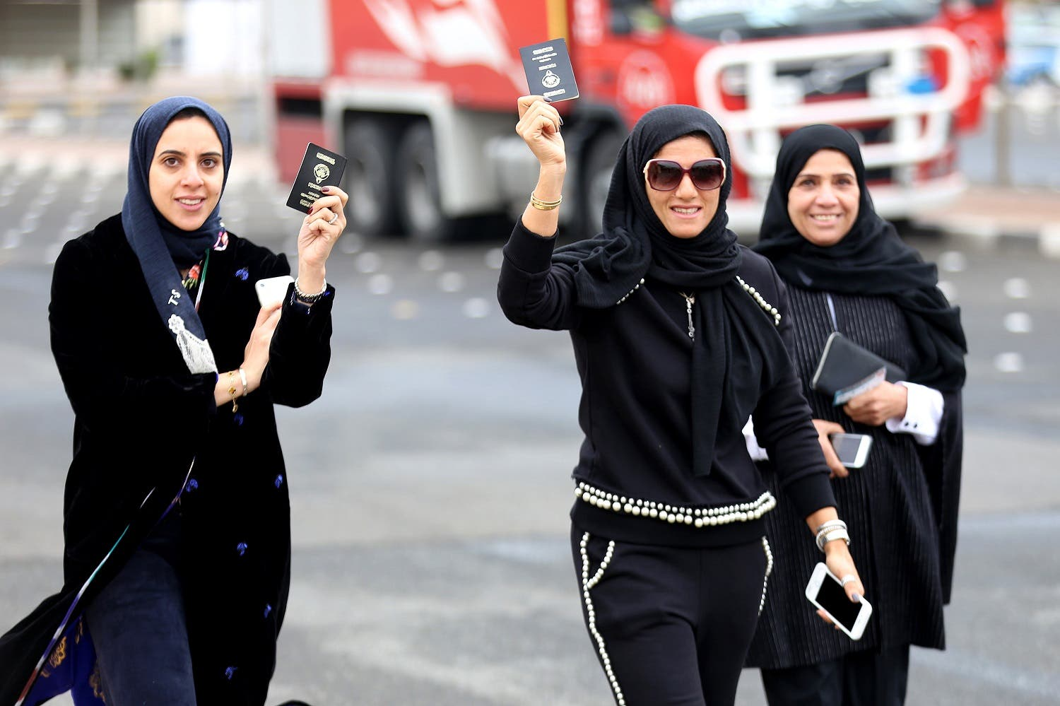 Kuwaiti women flash their passports as they arrive to cast their votes at a polling station in Kuwait City. (AFP)