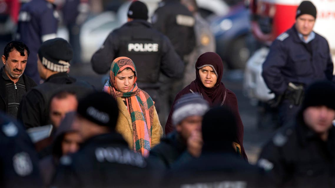 Migrants walk among Bulgarian riot policemen inside the Harmanli Refugee center, near the Bulgarian border with Turkey on November 25, 2016. Around 1,500 migrants have rioted in Bulgaria's largest refugee camp, triggering clashes that left two dozen policemen injured and prompted the arrest of hundreds of protesters, officials said. NIKOLAY DOYCHINOV / AFP