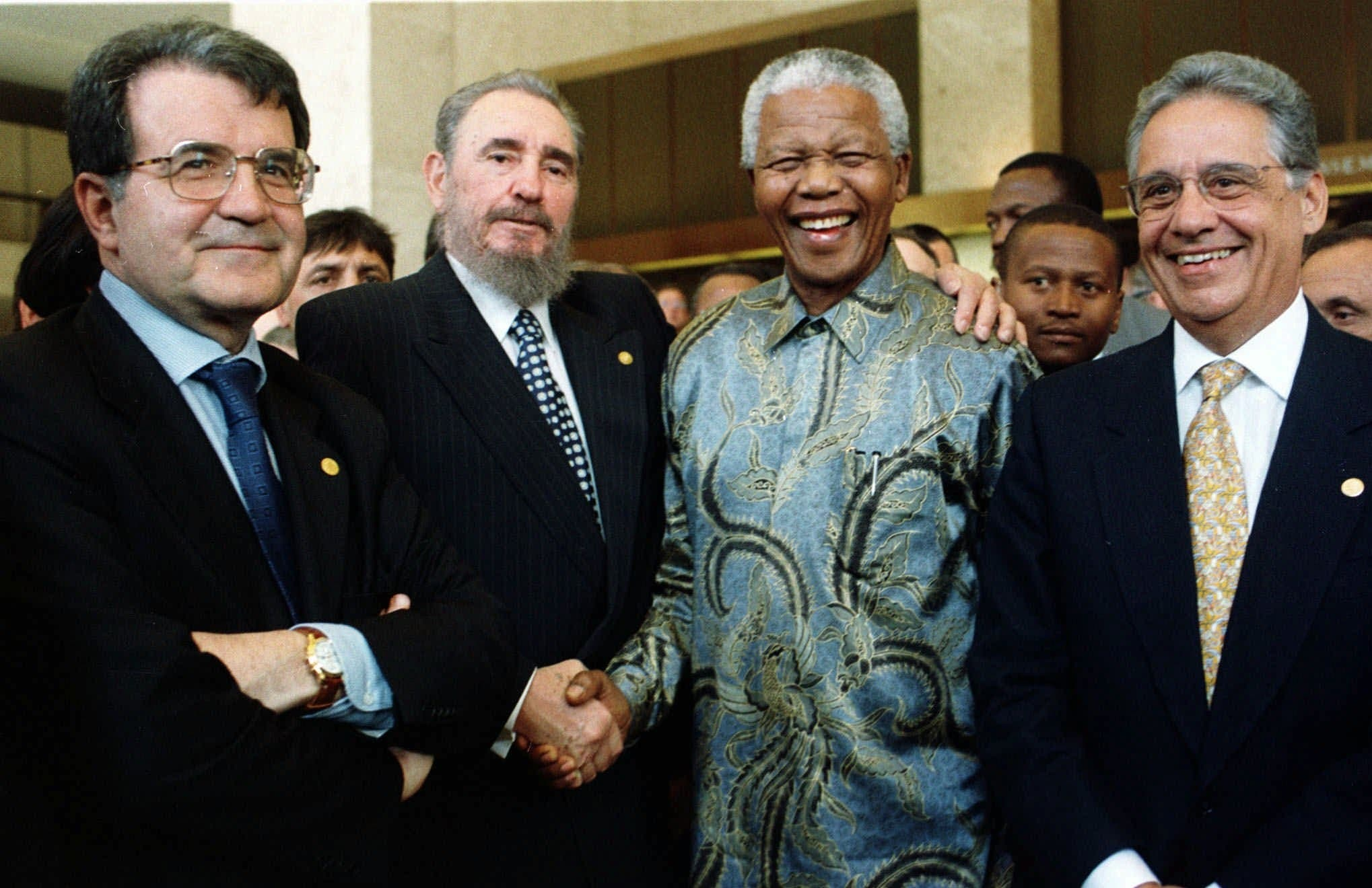Cuban President Fidel Castro, second left, shakes the hand of a laughing Nelson Mandela, as Italian Prime Minister Romano Prodi, 1st left, and Brazilian President Fernando Henrique Cardoso, right, look on at the 50th anniversary ceremony of the GATT Agreement, during the ministerial conference of the WTO (World Trade Organisation) held in Geneva,Tuesday May 19, 1998. (AP)
