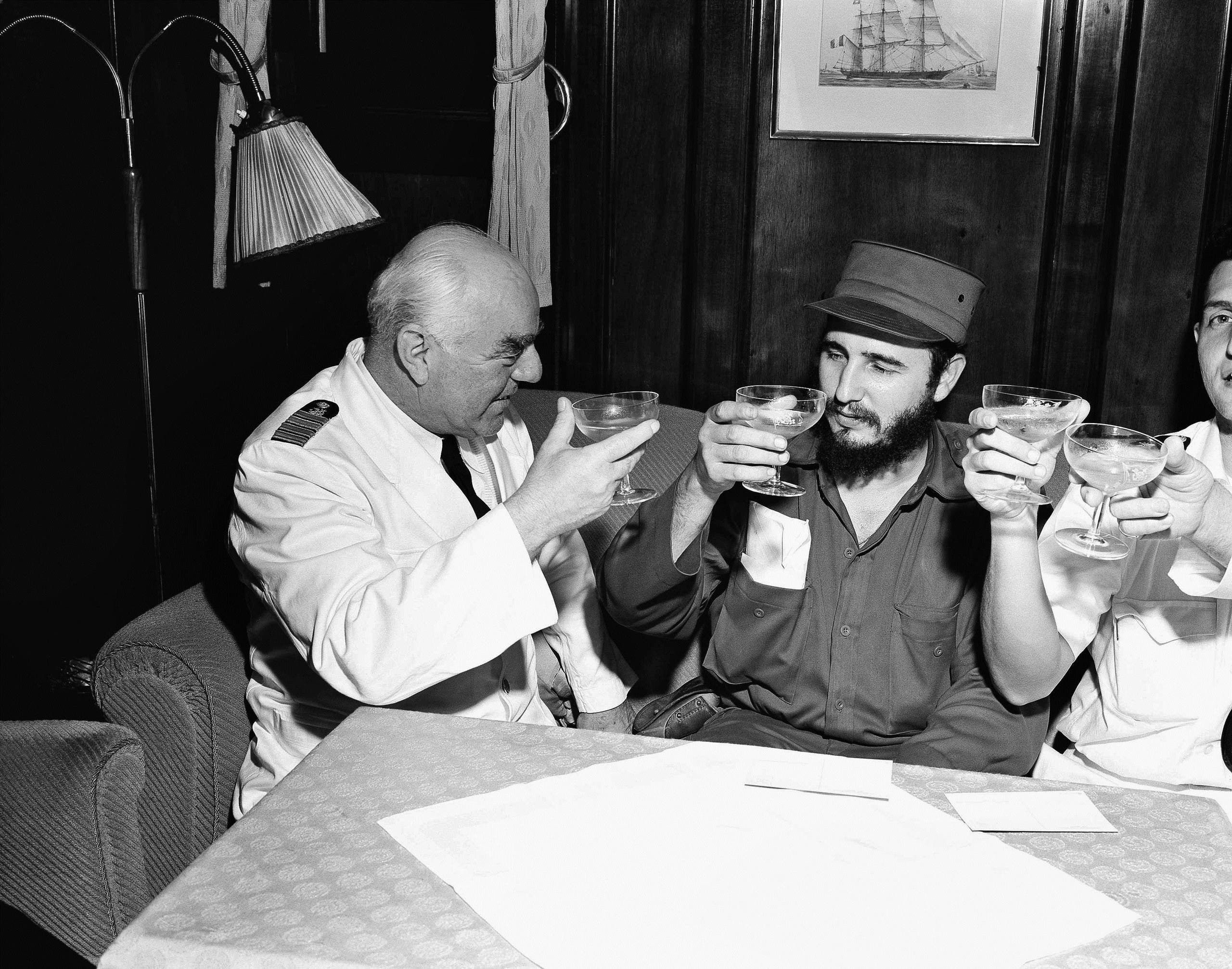 Captain Heinrich Lorenz, left, of cruise ship MS Berlin, proposes a toast to the success of Fidel Castro's government in Cuba, April 15, 1954, Havana, Cuba. Castro visited the North German Lloyd ship after it landed in Havana from New York. (AP)