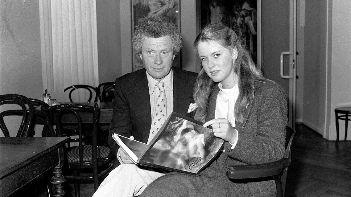 """British world-famous photographer and film director David Hamilton holds his book """"Tender Cousins"""" as he introduces the 16-year-old West German schoolgirl Anja Schuete to the press at Hamburg, Wednesday, March 11, 1981. (AP)"""