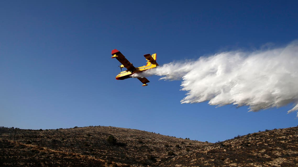 A foreign firefighting plane helps extinguish a fire as it flies over the village of Nataf close to Jerusalem, as it helps extinguish an ongoing fire in the area, on November 26, 2016. Wildfires near Jewish settlements in the occupied West Bank have forced hundreds to flee their homes, after mass evacuations in Israel and more than a dozen arrests, police said, while Israeli and Palestinian firefighters, helped by foreign aircraft, have been battling dozens of bush blazes fed by drought and high winds that have seen tens of thousands of people evacuated.  AHMAD GHARABLI / AFP