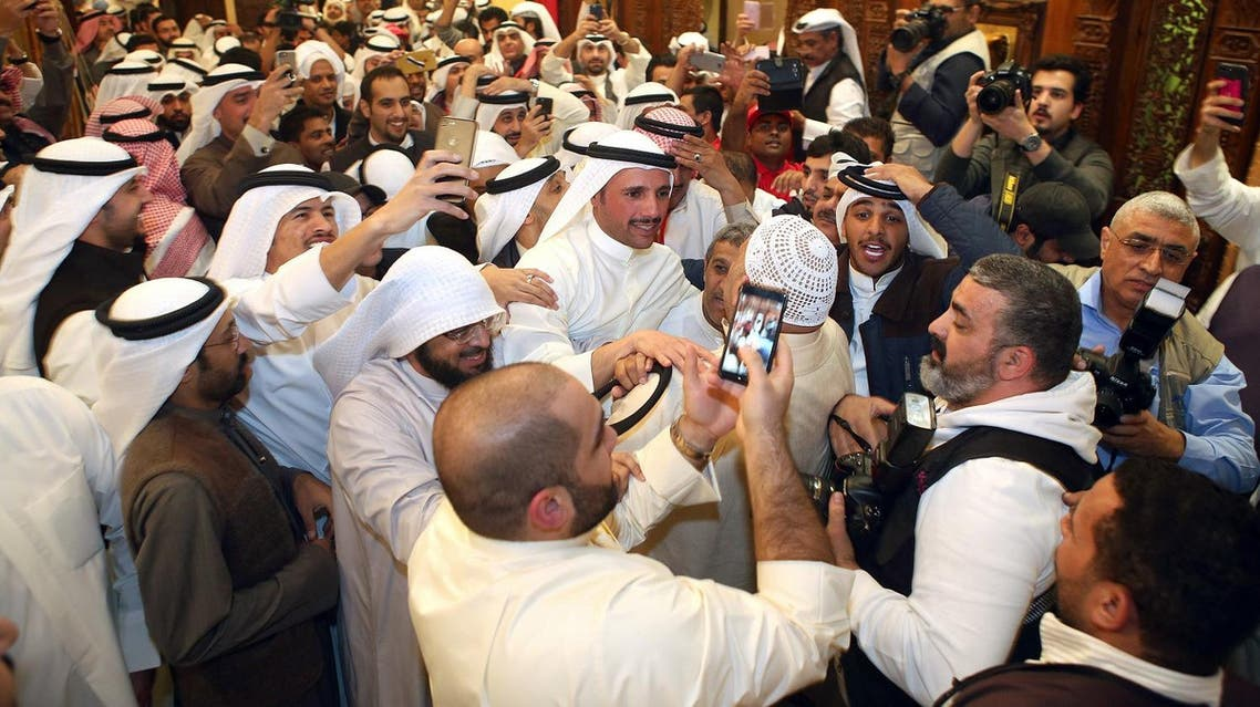 Kuwaiti candidate and former parliament speaker Marzouq al-Ghanem (C), celebrates with his supporters following his victory. (AFP)