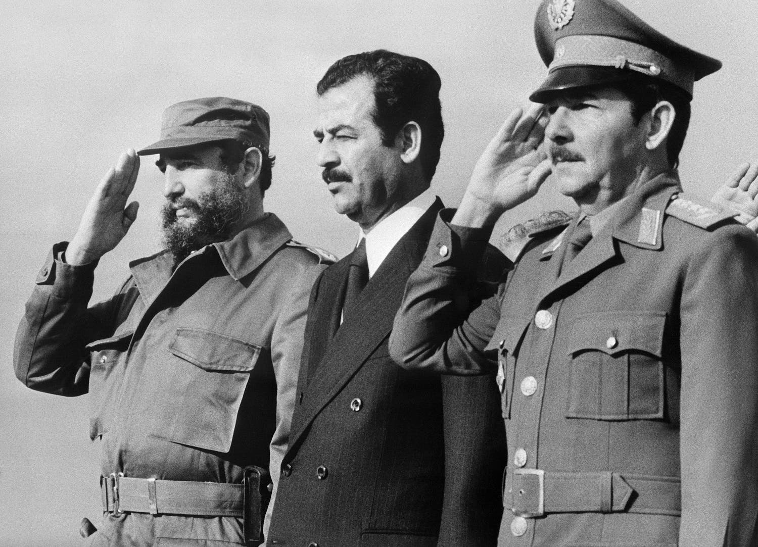 This handout photo taken and released by Prensa Latina on January 30, 1979 in Havana, shows Iraqi vice-president Saddam Hussein (C) standing during his visit to Cuba with Cuban President Fidel Castro (L) and Defense minister General Raul Castro. Cuban revolutionary icon Fidel Castro died late on November 25, 2016 in Havana, his brother announced on national television. PRENSA LATINA / AFP