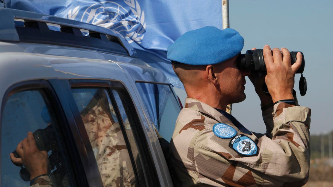 A UN member looks through binoculars to monitor the Israel-Syria border in the Israeli-annexed Golan Heights, on November 27, 2016, following an attack by gunmen linked to the Islamic State (IS) group. Israeli forces killed four gunmen linked to the Islamic State group after they fired on soldiers, the military said, in the first such attack on the occupied Golan Heights. AFP