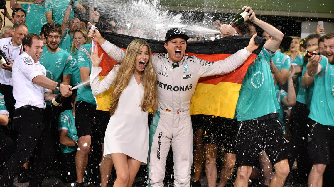 Staff members of Mercedes AMG Petronas F1 Team spray German driver Nico Rosberg (C-R) and his wife Vivian Sibold with champagne as they celebrate at the end of the Abu Dhabi Formula One Grand Prix at the Yas Marina circuit on November 27, 2016. Nico Rosberg won his maiden Formula One world title by securing second place behind his Mercedes arch-rival Lewis Hamilton in the Abu Dhabi Grand Prix. Andrej ISAKOVIC / AFP
