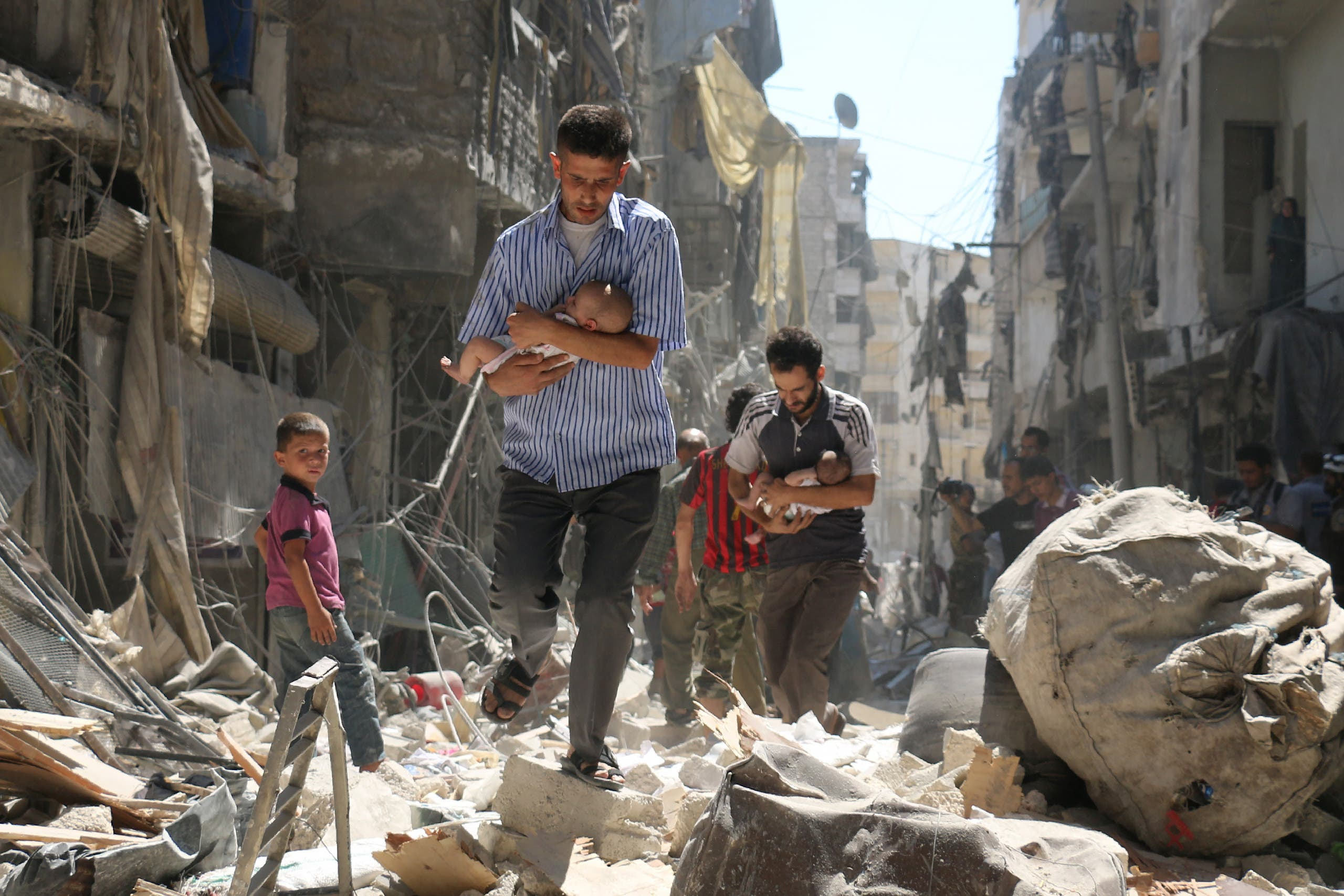 Syrian men carrying babies make their way through the rubble of destroyed buildings following a reported air strike on the rebel-held Salihin neighbourhood of the northern city of Aleppo, on September 11, 2016. Air strikes have killed dozens in rebel-held parts of Syria as the opposition considers whether to join a US-Russia truce deal due to take effect on September 12. AMEER ALHALBI / AFP