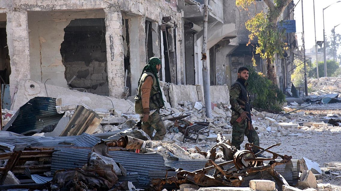 Syrian pro-government forces walk past destroyed buildings in the Baadeen district in eastern Aleppo on November 28, 2016, a day after they took control of the area from rebel fighters as part of their assault to retake the entire northern city. Government forces have retaken a third of rebel-held territory in Aleppo, forcing nearly 10,000 civilians to flee as they pressed their offensive to retake Syria's second city. In a major breakthrough in the push to retake the whole city, regime forces captured six rebel-held districts of eastern Aleppo over the weekend, including Masaken Hanano, the biggest of those in eastern Aleppo.  GEORGE OURFALIAN / AFP
