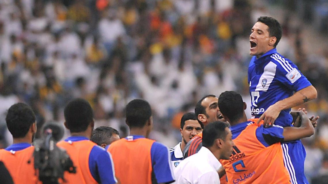 Saudi's Al-Hilal player Thiago Neves (R) celebrates with teammates after scoring against Al-Ittihad team during their Saudi Professional League football match at the King Fahad stadium in the capital of Riyadh, on September 20, 2013. AFP PHOTO/FAYEZ NURELDINE