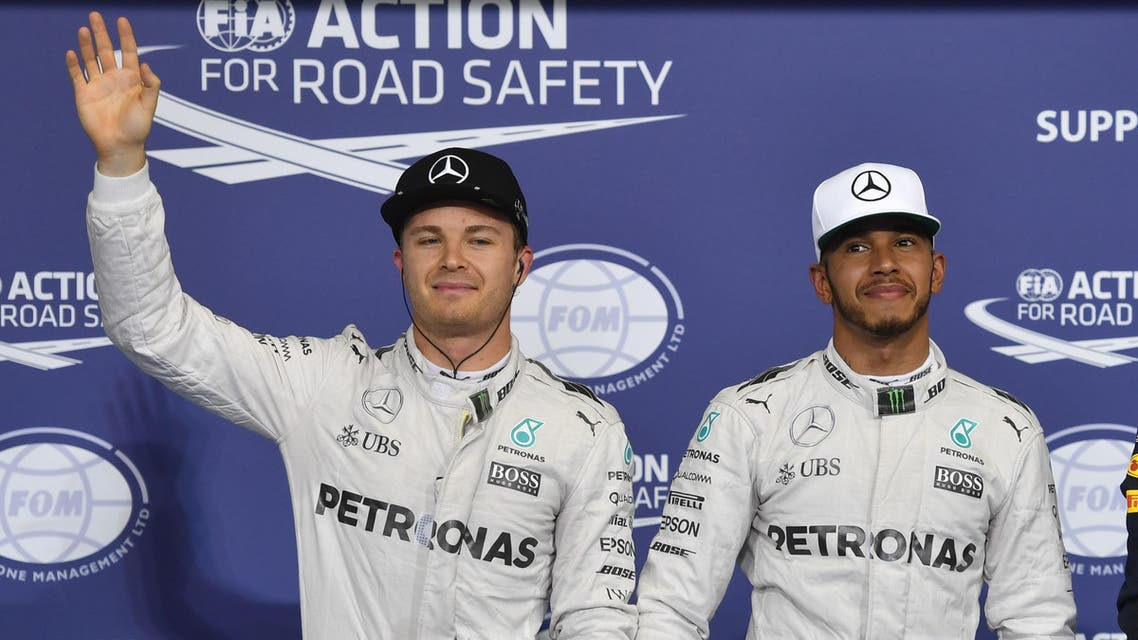 Mercedes AMG Petronas F1 Team's British driver Lewis Hamilton (C), flanked by his German teammate Nico Rosberg (L) and Infiniti Red Bull Racing's Australian driver Daniel Ricciardo, celebrate at the end of the qualifying session as part of the Abu Dhabi Formula One Grand Prix at the Yas Marina circuit on November 26, 2016. Lewis Hamilton will start on pole for the Abu Dhabi Grand Prix title showdown after the defending champion bettered his Mercedes teammate Nico Rosberg in qualifying. Red Bull's Daniel Ricciardo came in third to start on the second row at Yas Marina where the Australian is joined by the Ferrari of Kimi Raikkonen. Andrej ISAKOVIC / AFP