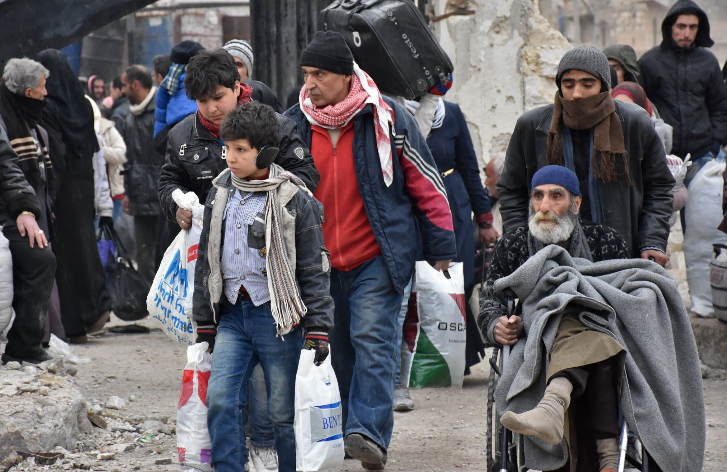 Syrian residents fleeing the eastern part of Aleppo gather in Masaken Hanano, a former rebel-held district which was retaken by the regime forces last week, on November 30, 2016. afp