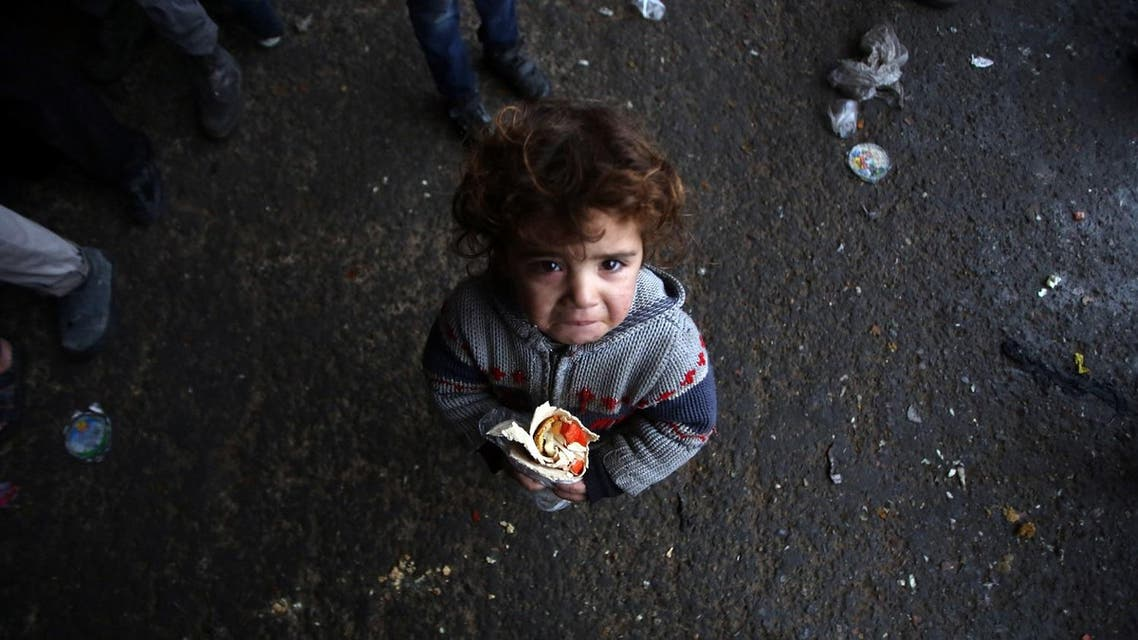 A Syrian child, who fled with his family from rebel-held areas in the city of Aleppo, reacts as he holds a sandwich. (AFP)