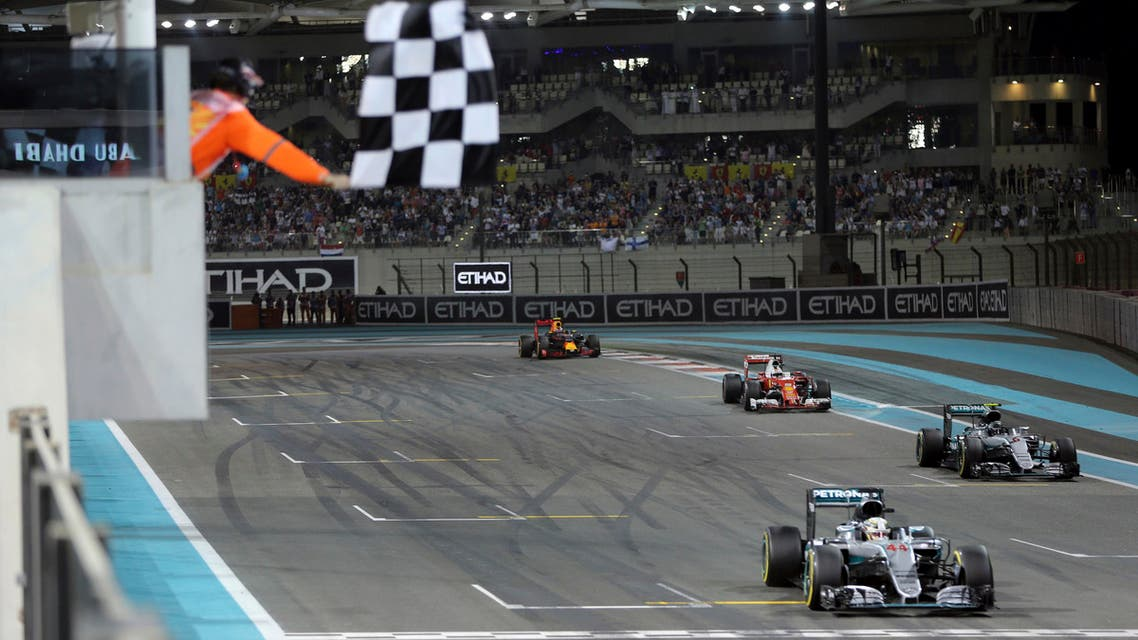 The checkered flag is waved as Mercedes driver Lewis Hamilton of Britain prepares to cross the finish line to win the Emirates Formula One Grand Prix at the Yas Marina racetrack in Abu Dhabi, United Arab Emirates, Sunday, Nov. 27, 2016. (AP)
