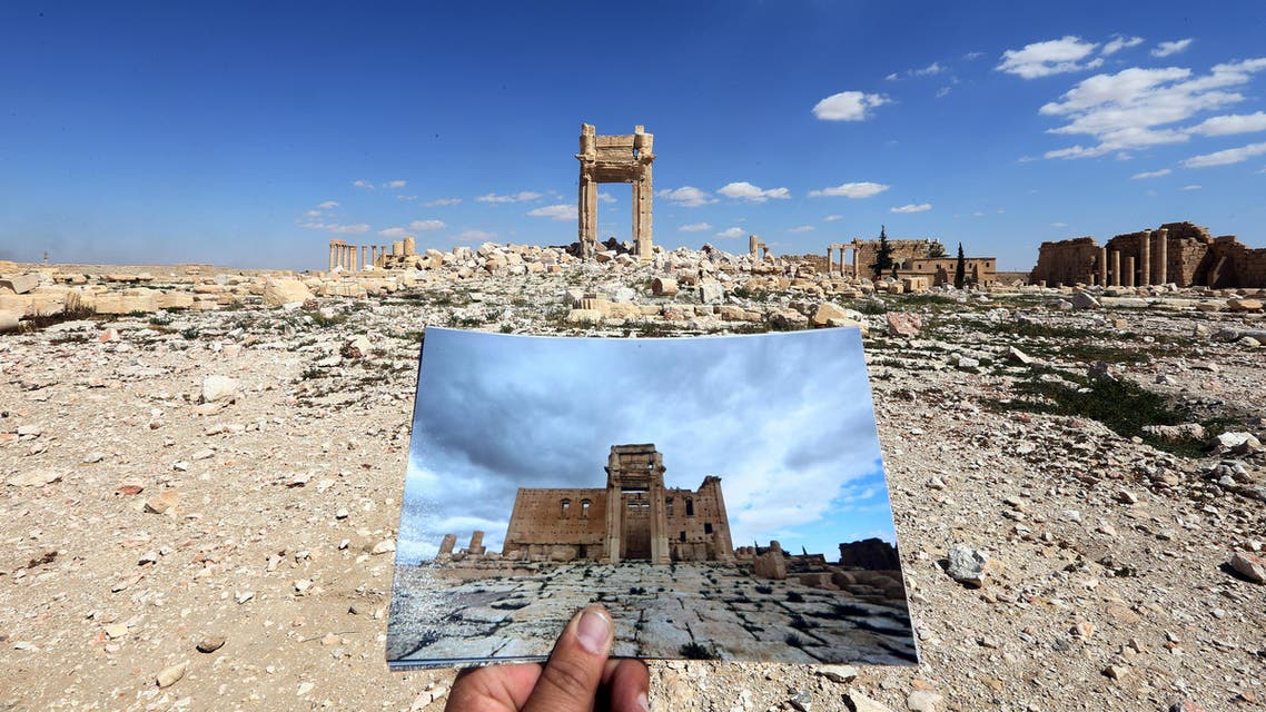 A general view taken on March 31, 2016 shows a photographer holding his picture of the Temple of Bel taken on March 14, 2014 in front of the remains of the historic temple after it was destroyed by Islamic State (IS) group jihadists in September 2015 in the ancient Syrian city of Palmyra. AFP