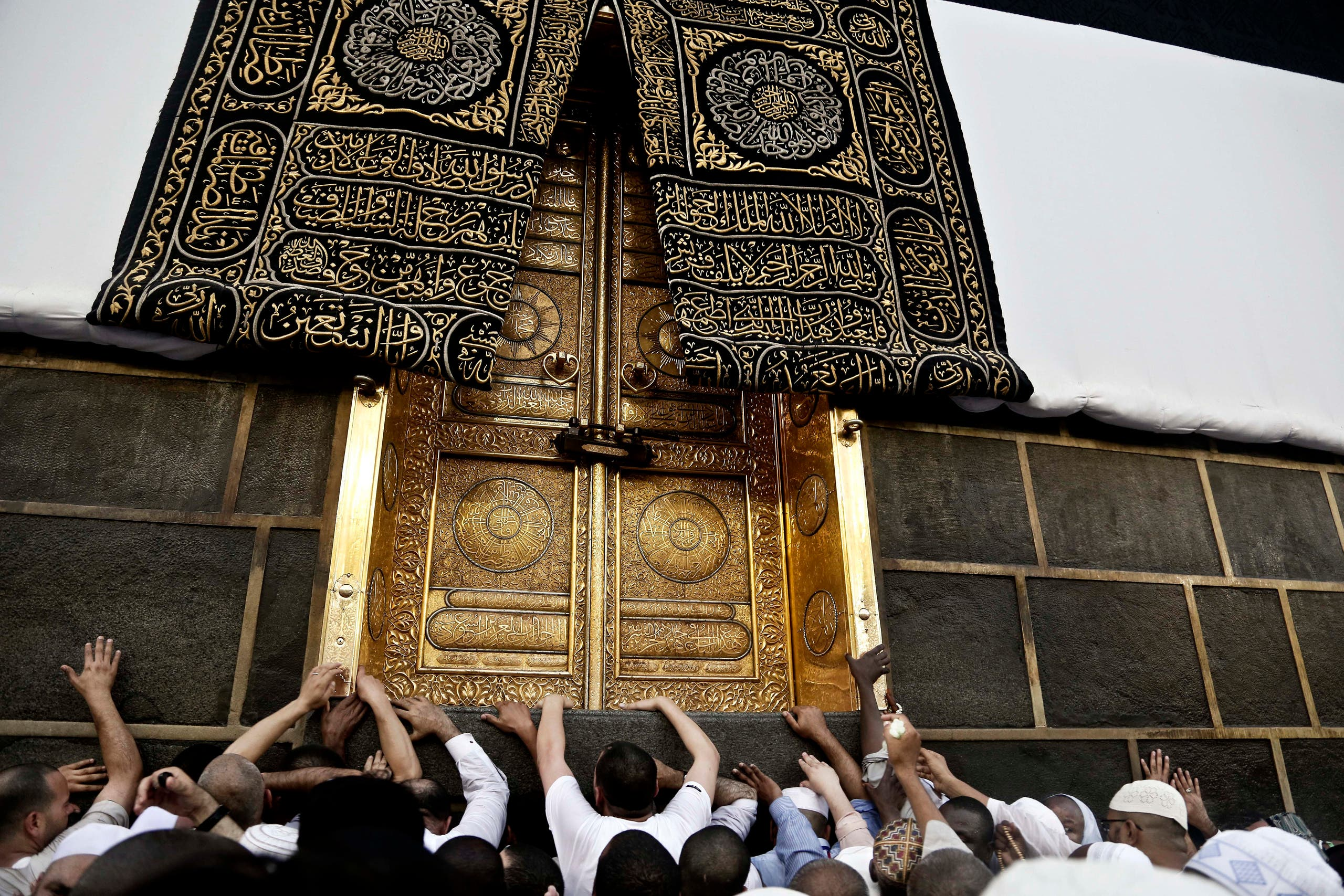 Muslim pilgrims touch the golden door of the Kaaba, Islam's holiest shrine, at the Grand Mosque in the Muslim holy city of Mecca, Saudi Arabia, Wednesday, Sept. 7, 2016. Millions of pilgrims have arrived to Mecca ahead of the Hajj annual pilgrimage which begins Saturday, Sept. 10, 2016. (AP)
