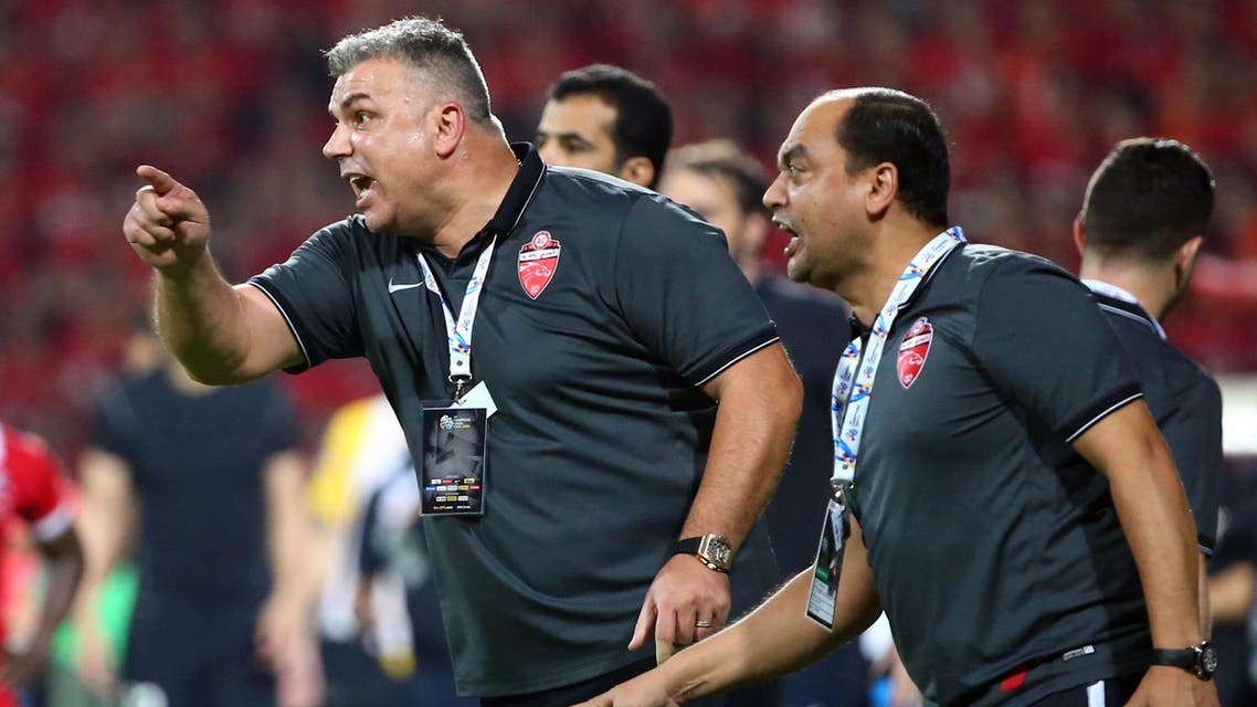 UAE's Al-Ahli Romanian manager Cosmin Olaroiu (L) shouts instructions to his players during the first leg match of the AFC Champions League football final against China's Guangzhou Evergrande at the Rashid Stadium in Dubai on November 7, 2015. The second leg of the final will take place on November 21 in China. AFP PHOTO / MARWAN NAAMANI  MARWAN NAAMANI / AFP