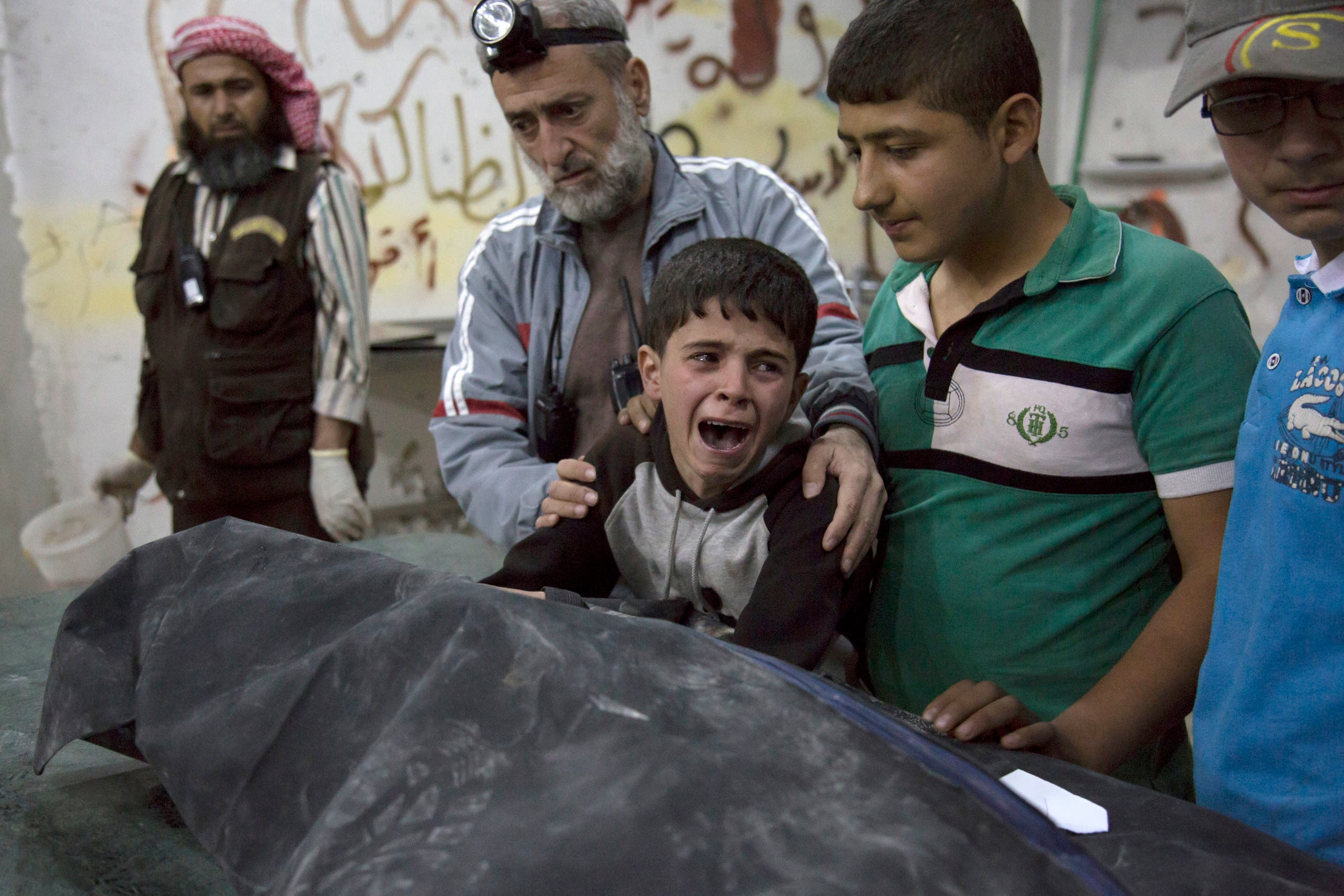 A Syrian boy is comforted as he cries next to the body of a relative who died in a reported airstrike on April 27, 2016 in the rebel-held neighbourhood of al-Soukour in the northern city of Aleppo.  KARAM AL-MASRI / AFP
