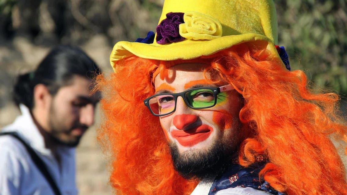 This undated photo courtesy of Ahmad al-Khatib, a media activist in Aleppo, shows Syrian social worker Anas al-Basha, 24, dressed as a clown, distributing toys to children in Aleppo, Syria. AP
