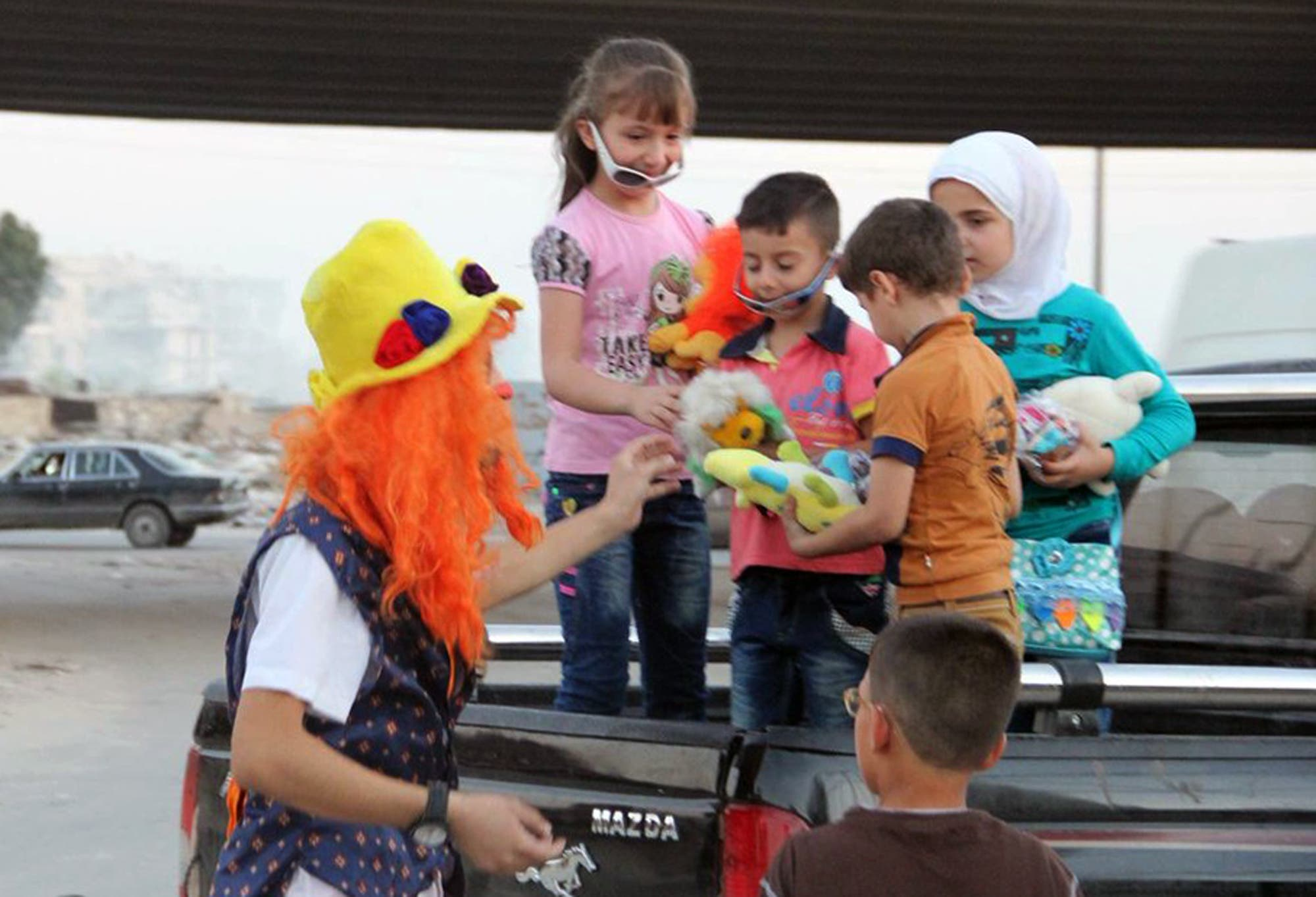This undated photo courtesy of Ahmad al-Khatib, a media activist in Aleppo, shows Syrian social worker Anas al-Basha, 24, dressed as a clown, distributing toys to children in Aleppo, Syria. AP