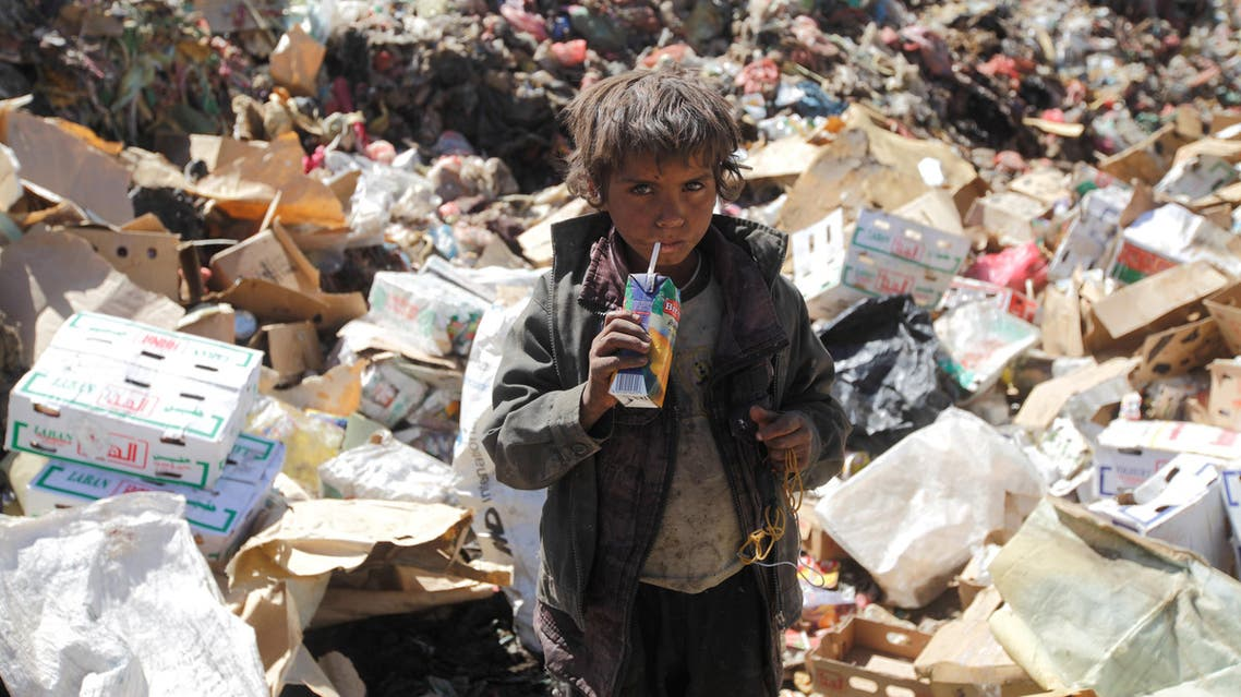 A boy drinks expired juice on a pile of rubbish at landfill site on the outskirts of Sanaa, Yemen November 16, 2016. REUTERS
