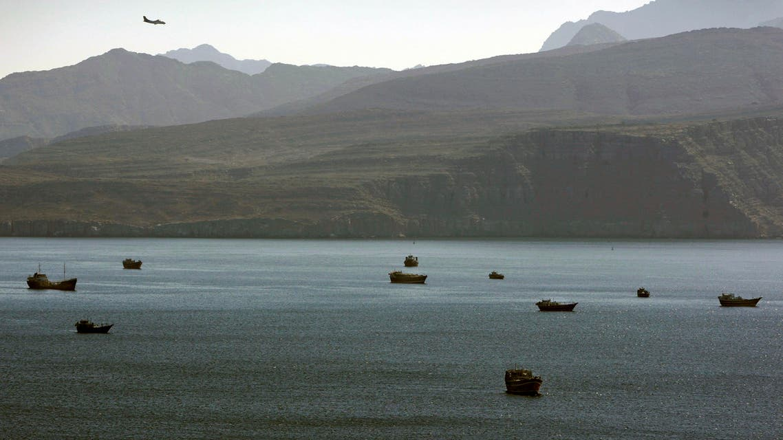 In this Jan. 19, 2012 photo, a plane flies over the mountains in south of the Strait of Hormuz as the trading dhows and ships are docked on the Persian Gulf waters near the town of Khasab, in Oman.  ap