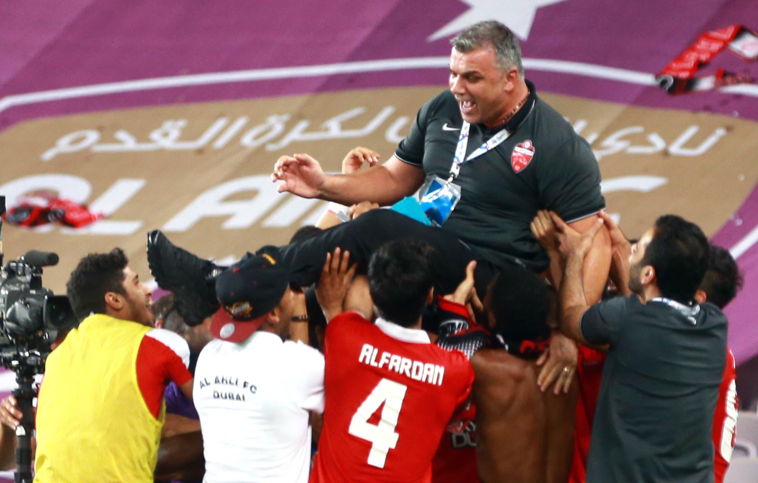Al-Ahli team celebrating with their coach Aurelian Cosmin Olaroiu (C) during their AFC Champions League football match at Sheik Hazza Bin Zayed stadium in Al-Ain, on May 27, 2015. AFP
