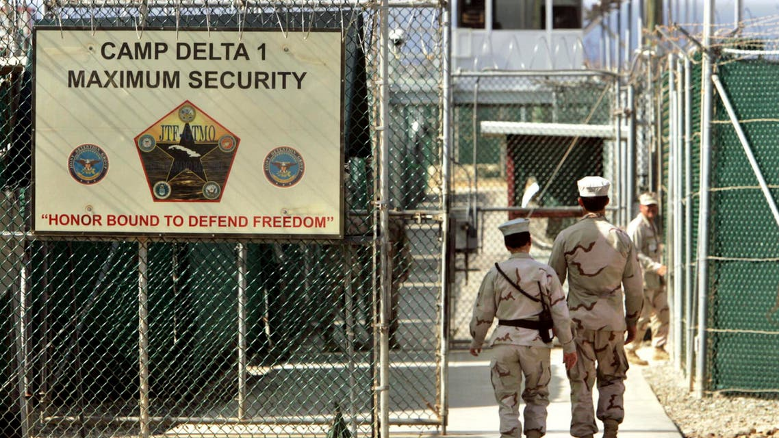 In this June 27, 2006 file photo, reviewed by a U.S. Department of Defense official, U.S. military guards walk within Camp Delta military-run prison, at the Guantanamo Bay U.S. Naval Base, Cuba. AP