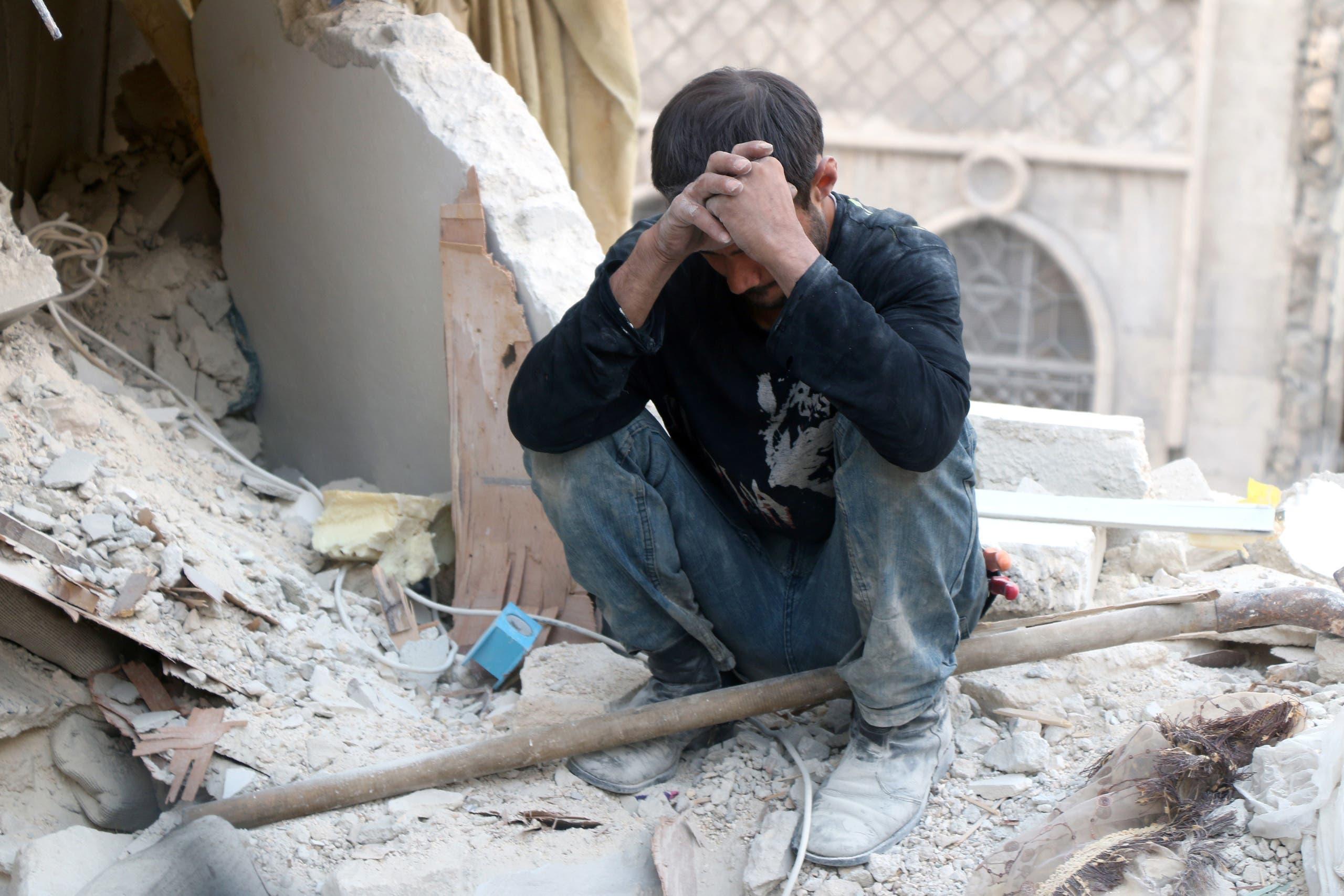 سوري يجلس على حطام منزله بحلب